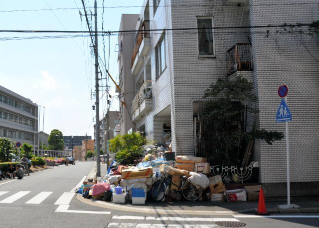 ゴミであふれた男性の住宅(右)。道路を挟んで病院がある=13日、名古屋市中区、三上元撮影