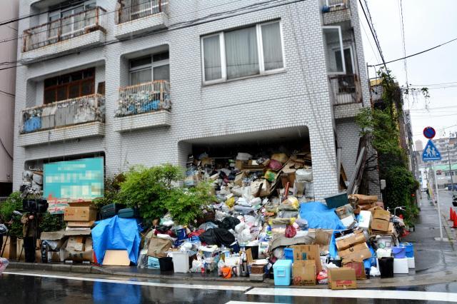 空き缶や段ボールなどのゴミが歩道まであふれた男性の住宅。玄関はふさがり、2階のベランダにもゴミが見える(画像の一部を加工しています)=12日、名古屋市中区、三上元撮影