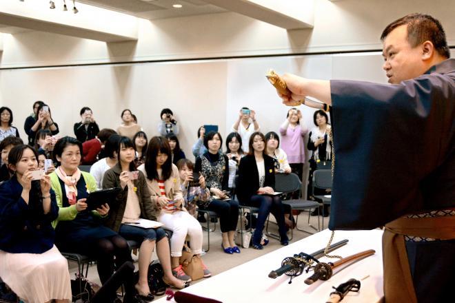 徳川美術館で開かれた刀剣についてのイベントで、模造刀を手に説明する学芸員。参加したのはほとんどが女性だった=4月18日、名古屋市東区徳川町