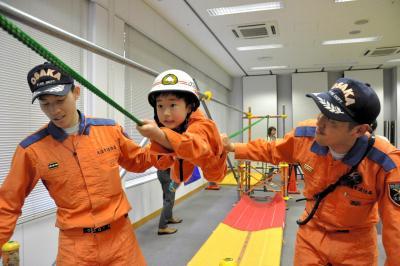 レスキュー隊員に支えられ、ロープ渡りを体験する子ども=2015年5月2日、大阪市阿倍野区