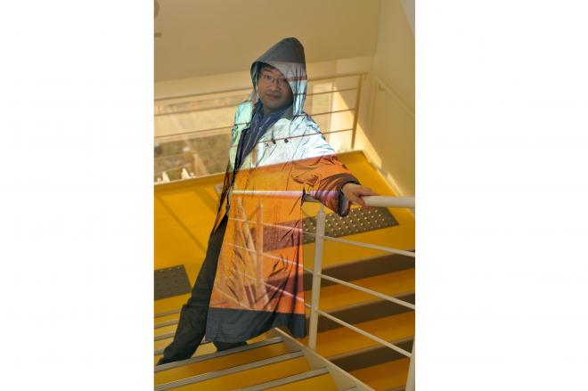 「光学迷彩」の技術を使ったマントを着た慶応大学大学院の稲見昌彦教授。背景に体が溶け込んでいるように見える=稲見教室提供、Ken Straiton撮影