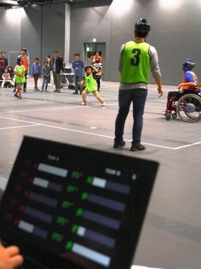 機械やコンピューターを駆使したドッジボール。手前の画面に各参加者の「生命力」が横棒で示され、何度かボールに当てられてゼロになると外野に移る。身体能力が高い人ほど「防御力」が低く、ボールに当たった時のダメージが大きいという設定だ。日本科学未来館であったイベントで市民が体験していた=東京都江東区