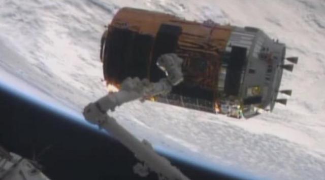 国際宇宙ステーション(下)のロボットアームが無人補給船「こうのとり」4号機に近づく様子=NASAテレビから