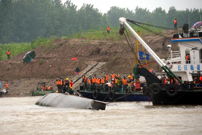 転覆した「東方之星」の船体の上に乗り、救助作業を続ける人たち=2015年6月3日、湖北省荊州市の長江、延与光貞撮影