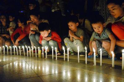 転覆事故で亡くなった犠牲者らのために、地元の人たちが公園に集まってろうそくに火をともした=2015年6月5日、中国湖北省荊州市監利県、延与光貞撮影