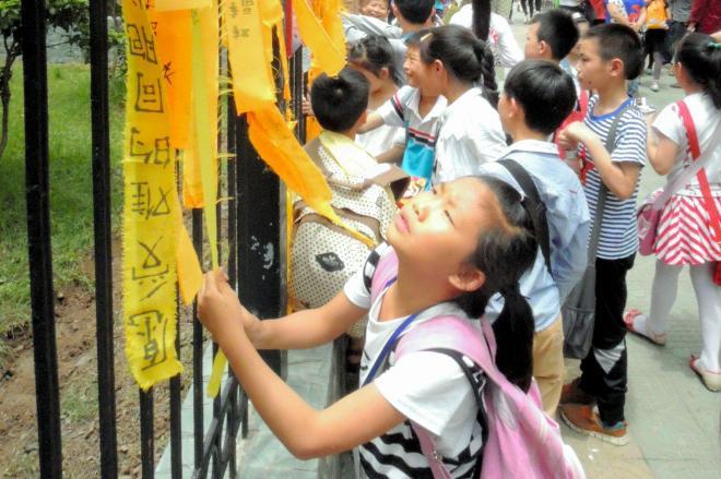 客船が沈没した荊州市監利県にある小学校の柵には、乗客の無事や犠牲者の冥福を祈るメッセージを書いた黄色いリボンが結ばれていた=2015年6月5日、金順姫撮影