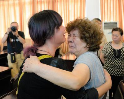 泣きながら抱き合う家族もいた=2015年6月6日、中国湖北省荊州市監利県、延与光貞撮影
