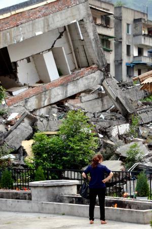 中国四川省の大地震があった北川チャン族自治県曲山。「震災遺跡」として残された街の前で線香をたむける女性=2013年5月10日
