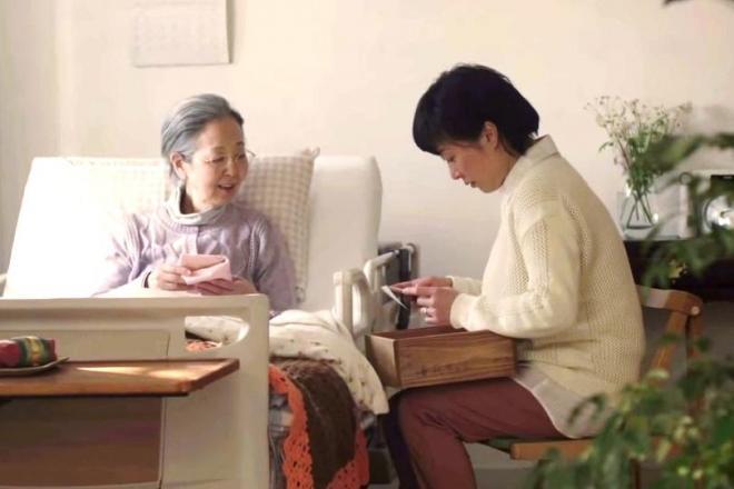 介護ベッドに座っているおばあさんと、その話に聴き入る女性