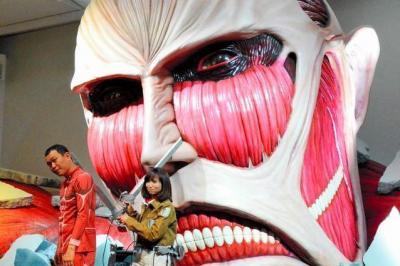 「進撃の巨人展」のオープニングセレモニーで、巨人の模型の前でポーズを取るタレントの吉木りさ(右)と千原せいじ=2014年11月27日
