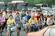 北京の朝のラッシュ時に、バスや車の合間を縫って自転車通勤する人たち=2008年7月30日、樫山晃生撮影