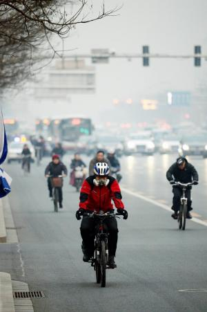 大きなマスクをした人が自転車で走り抜ける北京市中心部の幹線道路=2015年3月6日、北京市、関口聡撮影