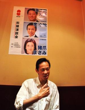 選挙への思いを語る李小牧氏。自身が経営する中華料理店には民主党の海江田万里氏と一緒に写ったポスターが貼られている