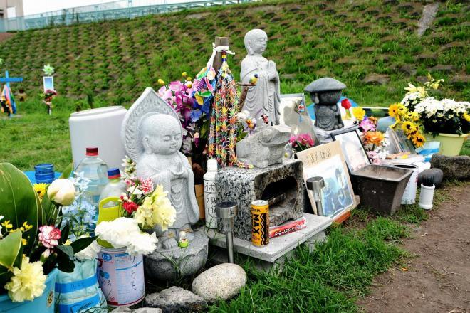 事件現場の河川敷には地蔵が置かれ、花が供えられている=16日、川崎市川崎区