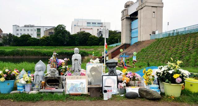 事件現場の河川敷には花や食べ物が供えられている=16日、川崎市川崎区