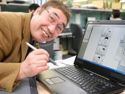 初めて手にしたパソコン入力ペンの筆致にもやっと慣れ、笑顔で4コマ漫画に挑戦する蛭子さん=2005年11月17日