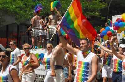 多様性の象徴であるレインボーフラッグを振って歩くゲイパレードの参加者ら=2012年6月、ニューヨーク