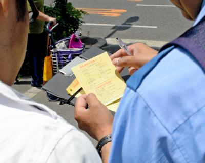 改正道路交通法が6月1日から施行され、危険な運転をした自転車運転者へ黄色い指導カードが渡された=2015年6月1日、大阪市北区、遠藤真梨撮影