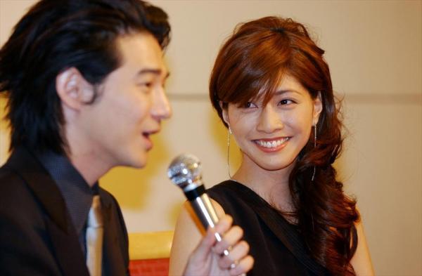 結婚会見で笑顔をみせる俳優の吉岡秀隆さんと内田有紀さん=2002年12月