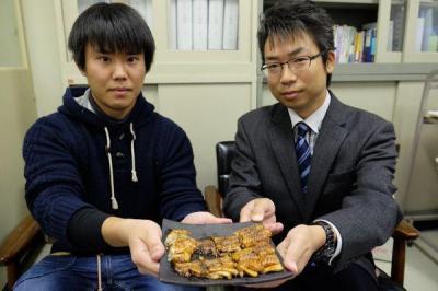 昨年11月、「ウナギ味のナマズ」の試作を手にする有路昌彦准教授(右)と研究者の和田好平さん(当時大学4年)=奈良市中町の近畿大学