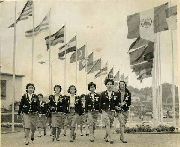 【1964年9月】東京五輪のコンパニオン。開村式でにぎわう選手村のメイン・ゲート付近