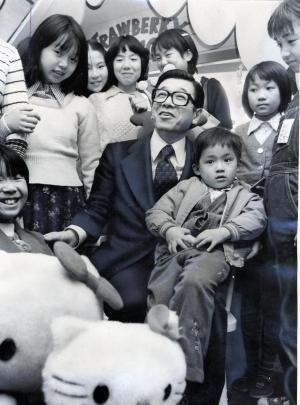 「いちごの王さま」サンリオ社長の辻信太郎さん。小さな「コンサルタント」と呼ぶ、子どもたちに囲まれ笑顔に=1976年12月