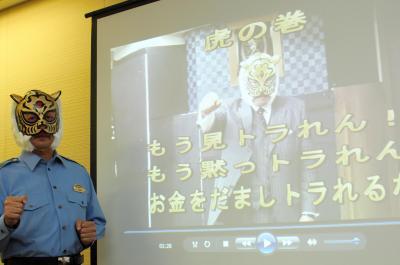 初代タイガーマスクの佐山聡さんが登場する詐欺被害防止の啓発動画と、覆面姿の警察官=2015年7月16日