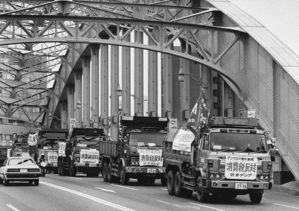 【1988年9月18日】全日自労建設一般労組の労働者によるダンプカー57台を連ねて永代橋を渡る消費税反対のダンプデモ