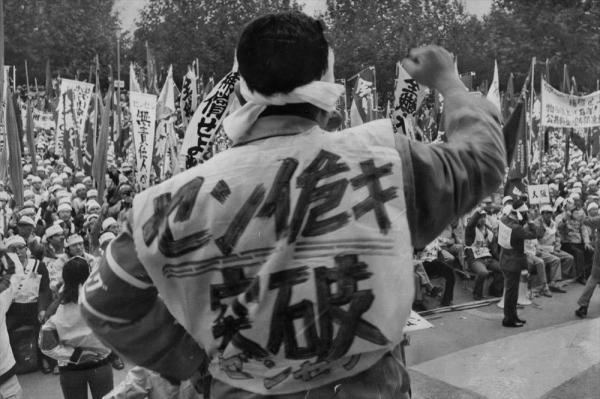 【1974年11月9日】ゼンセン同盟の「インフレ粉砕、繊維危機突破、雇用保険法実現中央集会」。「センイ危キ突破」のゼッケンをしてこぶしを突き上げる参加者。集会の後、国会までデモ行進した