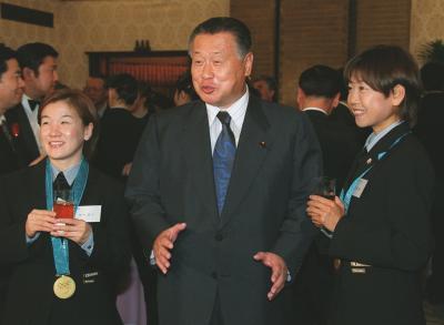 2000年10月3日、シドニー五輪金メダリストの田村亮子さん(左)、高橋尚子さん(右)に囲まれ、表情を崩す森喜朗氏