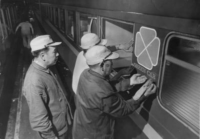 西鹿児島行急行「桜島」の1等車の表示の上に、四つ葉のクローバーを型どったマークを張り、グリーン車への変更作業をする国鉄職員=1969年