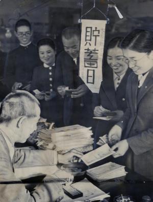 鳥取県庁の「必勝必成貯蓄組合」の貯蓄運動。「貯蓄日」の小旗が掲げられると所持金の5%を召し上げられる「不意討貯蓄」=1942年12月1日