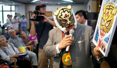 施設への寄贈のお礼に、ちぎり絵の似顔絵を受け取る初代タイガーマスクの佐山聡さん=2013年7月2日