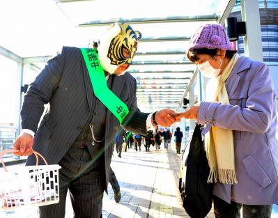 振り込め詐欺の被害防止をよびかけるチラシやグッズを配り歩く、初代タイガーマスクの佐山聡さん=2012年2月20日