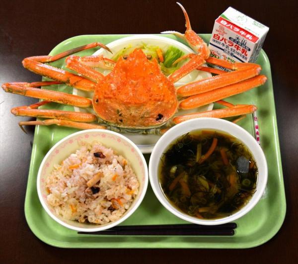 蒸した若松葉がにを主菜に、いかめし、もずく汁。地元の海の幸いっぱいの給食=2015年1月30日、鳥取県岩美町