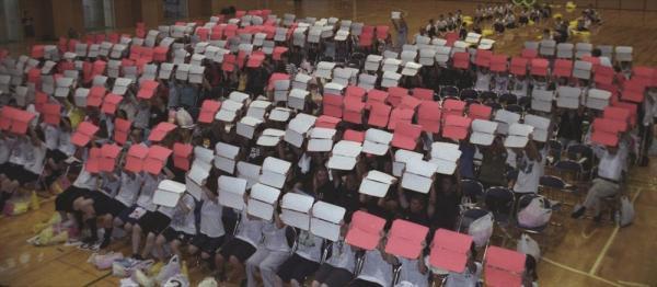 カラーブックを使い、人文字の応援練習をするPL学園の生徒たち=2004年8月10日、大阪府富田林市喜志の同校体育館で