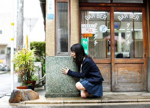 いけず石を愛してやまない高校生の吉田伊織さん。江戸時代の図絵などに見られる「車除(よ)け石」にさかのぼれる可能性が高く現在の目的も車よけが基本だという=京都市中京区