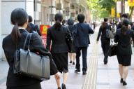 暑さの中、リクルートスーツに身を包み、大手企業の筆記試験会場を後にする就活生ら=2015年8月1日、福岡市中央区