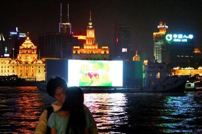 上海のデートスポットで、ロマンチックな雰囲気のカップルたちの後ろを、大光量を発して航行する広告船=2006年10月
