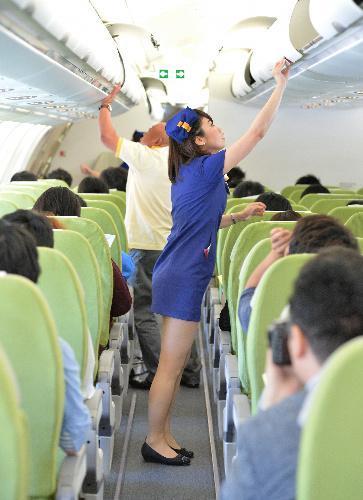 就航したスカイマークの新型機内で、新制服で業務する客室乗務員=2014年6月14日、福留庸友撮影