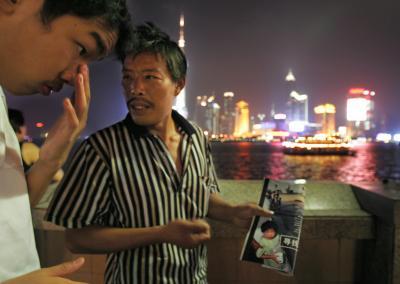 息子と思われる子どもの写真が載った雑誌を手に、夜遅くまで手がかりを求める父親=2005年10月、上海市で