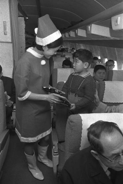 クリスマスイブ、日本航空の国内、国際線の機中で、赤いミニスカートスタイルのスチュワーデスのサンタさんが乗客全員にクリスマスプレゼントを贈った。プレゼントの中身はウイスキーとチョコレート=1968年12月24日