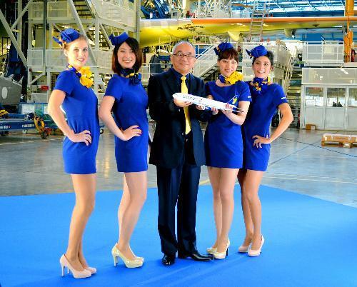 A330の模型を手にミニスカートの新制服を披露するスカイマークの西久保慎一社長(中央)=2013年12月13日