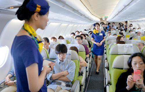新制服姿で客室乗務員が搭乗し、初就航したスカイマークの羽田発福岡行きの新型機=2014年6月14日