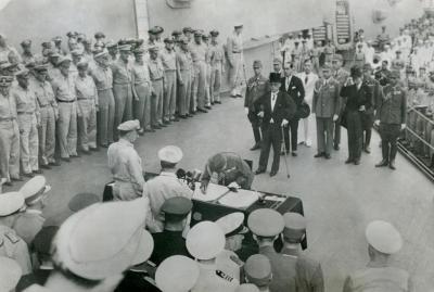 東京湾内のアメリカ戦艦「ミズーリ」の艦上で1945年9月2日、連合国軍最高司令官が提示した降伏文書に調印する日本の全権、陸軍参謀総長の梅津美治郎大将。テーブルの手前、後ろ向き右がマッカーサー元帥。その後方に並んでいるのは各国代表。向こう側は日本代表団。先頭はもう一人の全権、重光葵外相