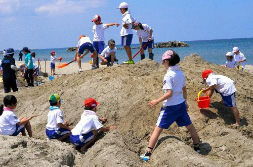 設計に沿って砂山を削り、ダイオウイカの足を造形する児童たち=鶴岡市の湯野浜海水浴場