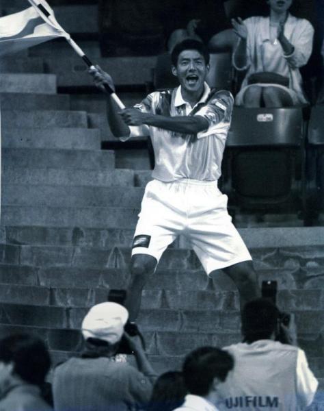 選手時代の松岡修造さん。1996年フェド杯で観客席から日の丸を振って、伊達公子選手に声援を送る=1996年4月28日
