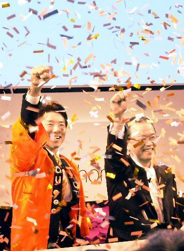 KDDI(au)のiPhone発売開始と同時に松岡修造さん(左)、田中孝司社長がガッツポーズした=2014年9月19日、東京都渋谷区