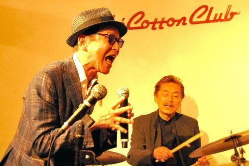 【1976年~】口でトランペットの演奏をするタモリさん。ドラムは菅原さん=2014年6月撮影
