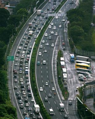 お盆の帰省や行楽の車で渋滞する東名高速の下り車線(左)=13日午前9時23分、横浜市緑区、池永牧子撮影